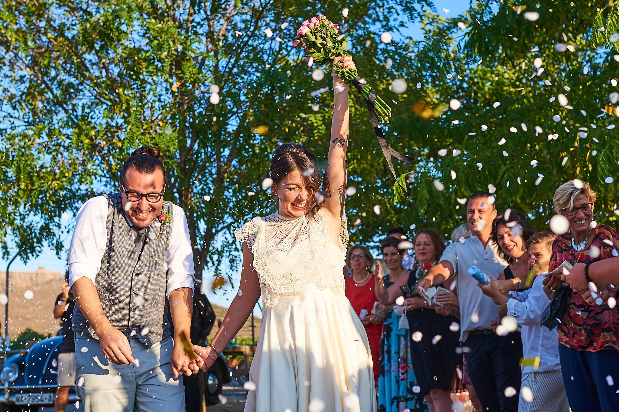 El equipo de Albamay felices después de casarse al aire libre y los invitados echando pétalos y arroz.